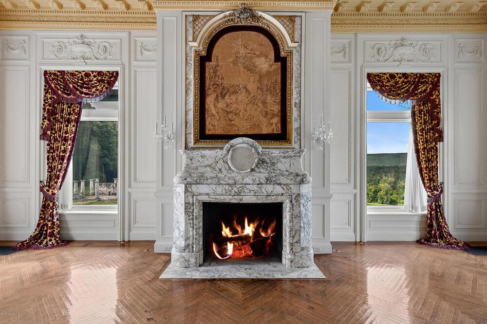 This is a closer look at the dining room fireplace with an elegant design to its mantle flanked with two large windows of the same tone as the mantelpiece. Image courtesy of Toptenrealestatedeals.com.