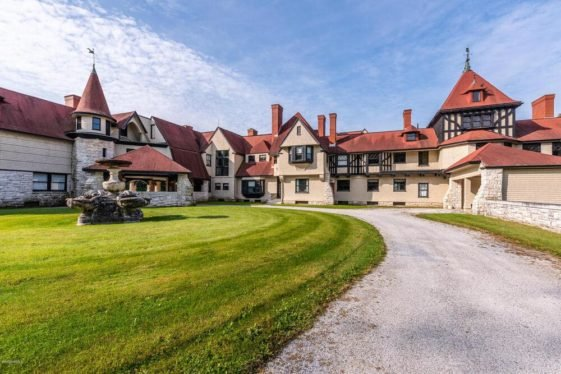 This is an exterior view of the front of the main house in the estate showcasing multiple chimneys and windows on its beige exterior and terracotta toned roofs. Image courtesy of Toptenrealestatedeals.com.