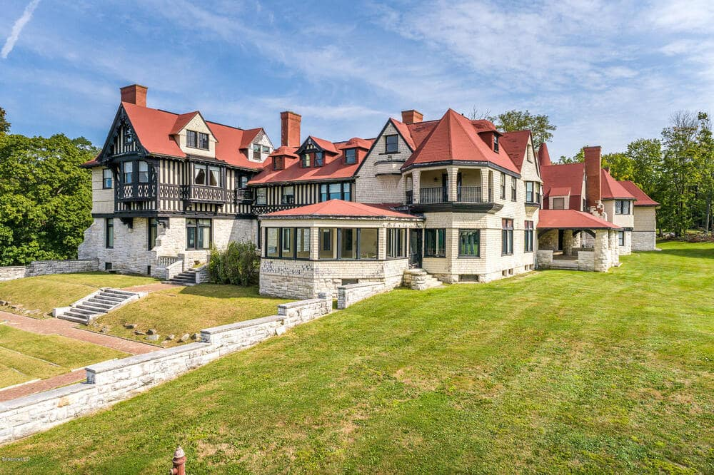 This is a closer look at the back of the main house showcasing the terracotta toned roofs, beige exterior walls and the multiple windows. Image courtesy of Toptenrealestatedeals.com.