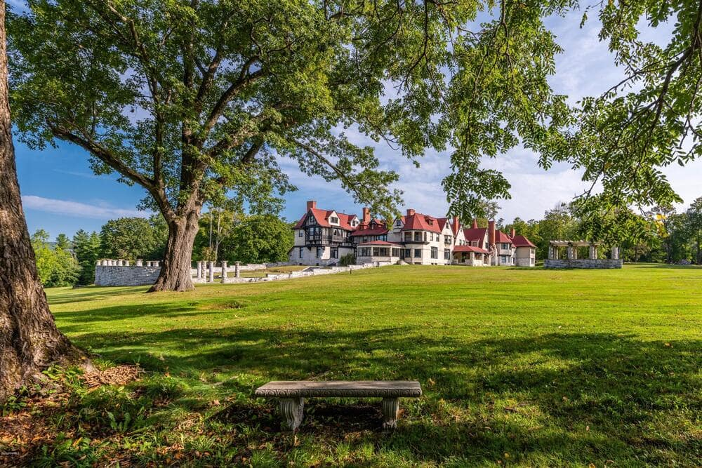 This is a farther view of the main house featuring the spacious lawn of grass lined with tall trees that bring color to the house exteriors. Image courtesy of Toptenrealestatedeals.com.
