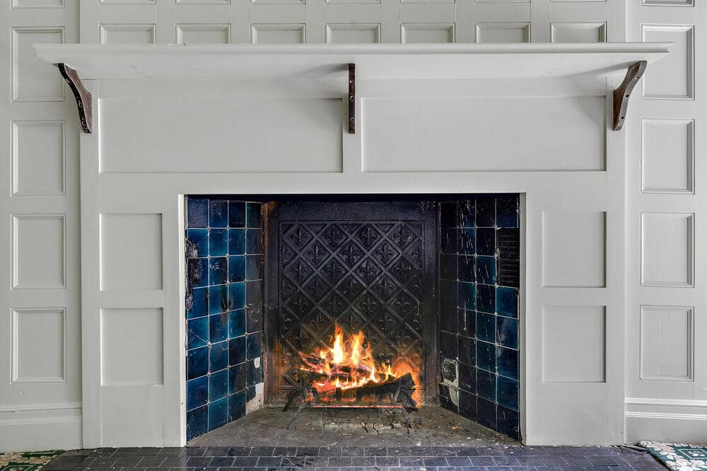 This is a closer look at one of the preserved fireplaces of the house that has a white tone to its mantle to blend with the surrounding paneled wall. Image courtesy of Toptenrealestatedeals.com.