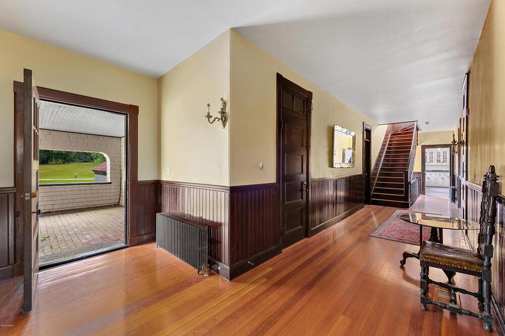 This hallway has a hardwood flooring to match the dark wainscoting of the beige walls. Image courtesy of Toptenrealestatedeals.com.
