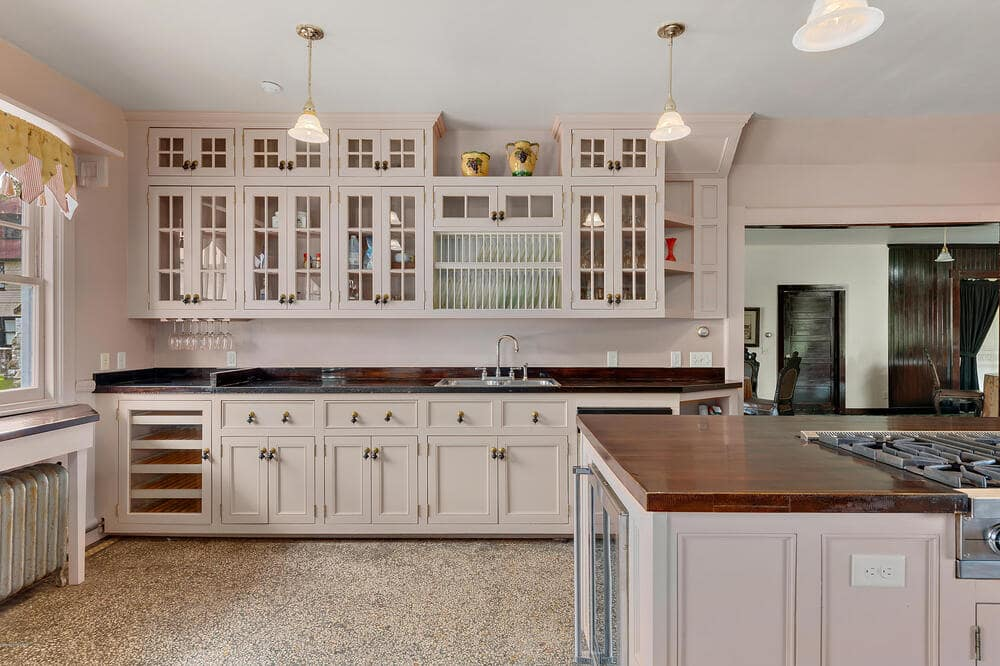 This is a close look at the kitchen and its bright cabinetry that blends well with the walls contrasted by the countertops. Image courtesy of Toptenrealestatedeals.com.