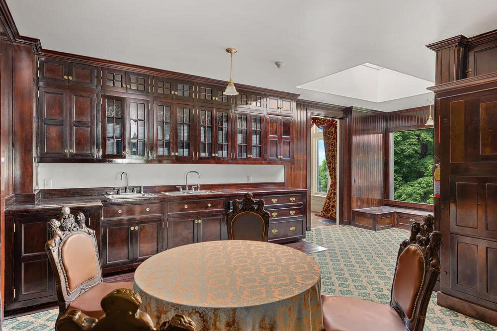 This end of the kitchen has an informal dining area in the middle and dark wooden cabinetry along the walls to contrast the backsplash. Image courtesy of Toptenrealestatedeals.com.