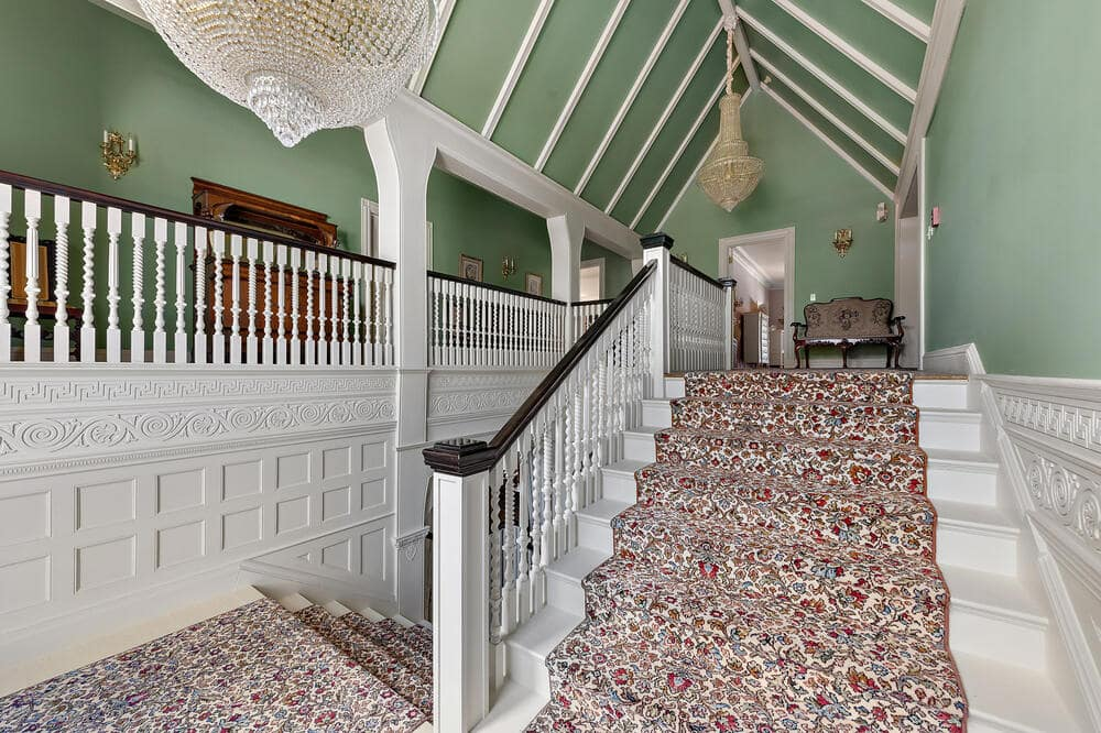 This is a look at the landing of the house with a carpeted staircase to contrast the white wooden railings and bannisters. Image courtesy of Toptenrealestatedeals.com.