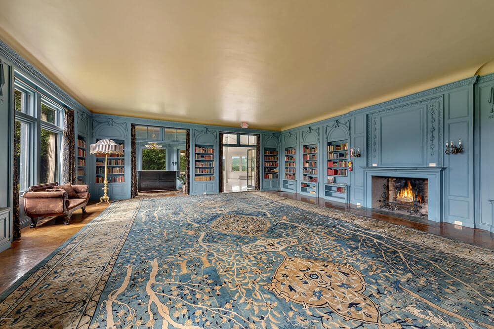 This is the library that has a large fireplace on one side of the built-in bookshelves on the gray-toned walls that match the patterned carpeting. Image courtesy of Toptenrealestatedeals.com.