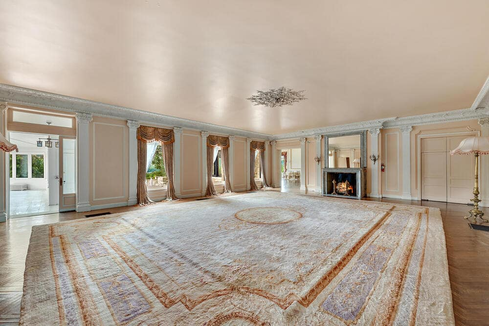 This is a look at the spacious and bright living room with a large patterned carpet to match the beige walls and ceiling adorned by the molding and natural lighting. Image courtesy of Toptenrealestatedeals.com.