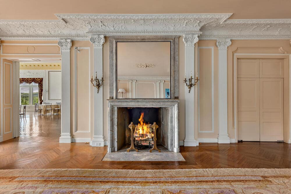 This is a closer look at the large fireplace at the far wall of the large living room with beige walls and elegant moldings. Image courtesy of Toptenrealestatedeals.com.