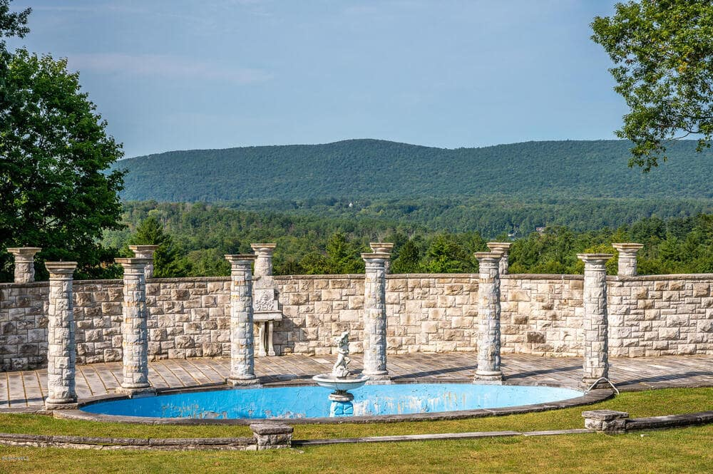 This is a view of the large swimming of the estate adorned with tall stone pillars and tall stone walls for a Mediterranean aesthetic. Image courtesy of Toptenrealestatedeals.com.