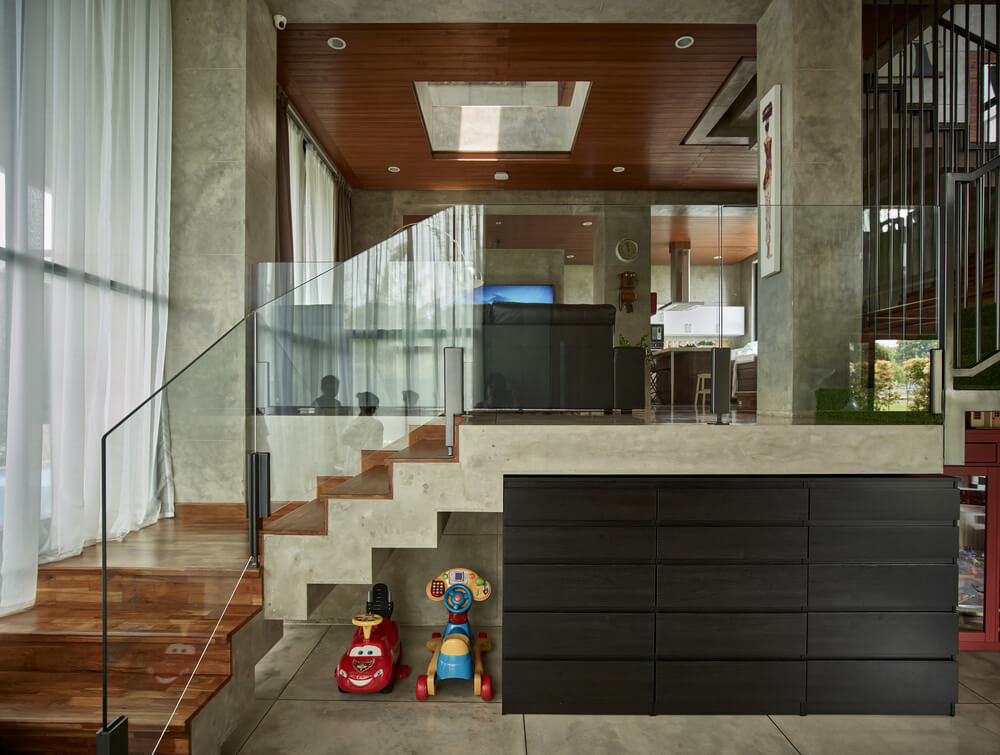 Upon entry, you are welcomed by this foyer that has a large black credenza cabinet next to the glass wall of the staircase that leads to the living room.