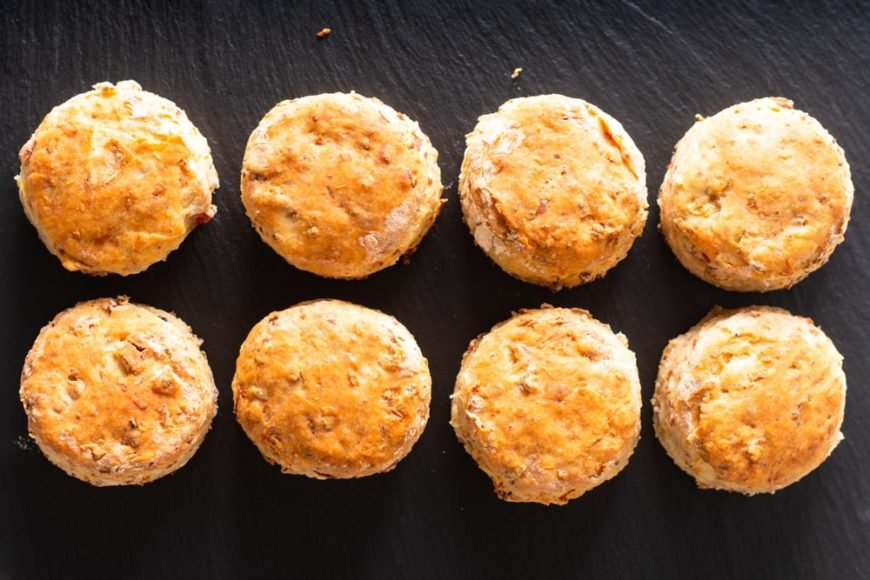 A set of eight ham and cheese scones on a black surface.