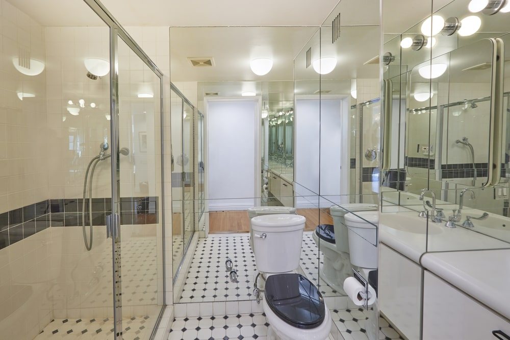 This bathroom has a glass-enclosed shower area across from the modern white vanity beside the toilet with a mirrored wall behind it. Image courtesy of Toptenrealestatedeals.com.