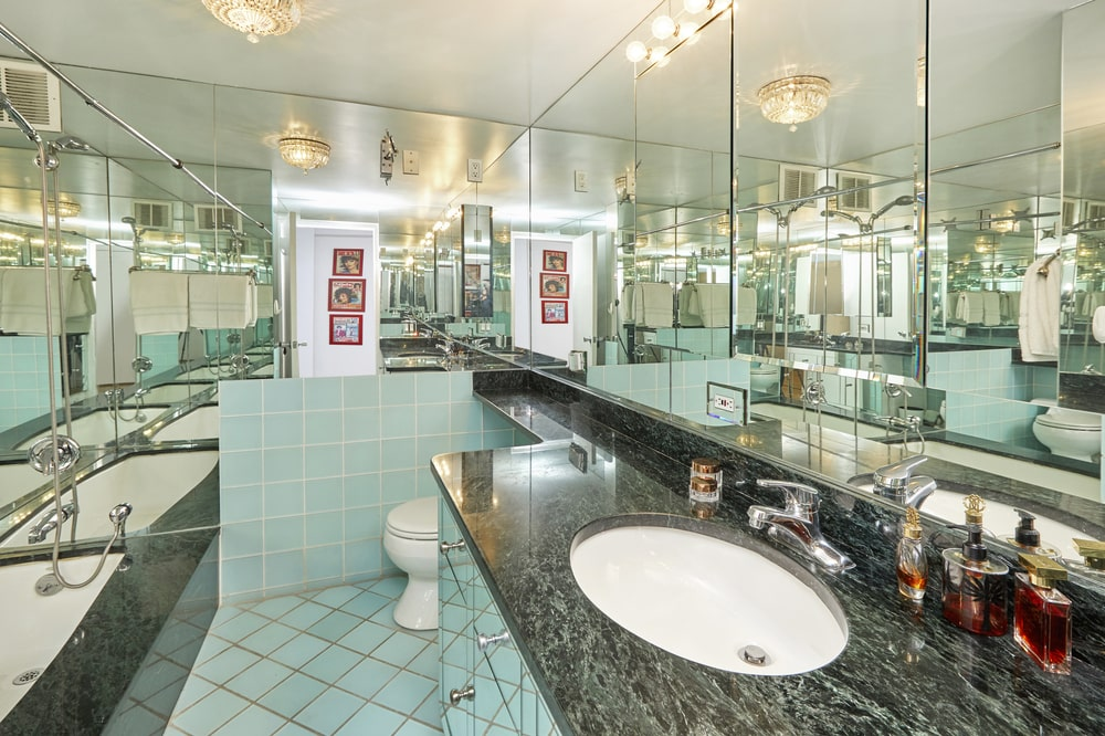This bathroom has a dark marble counter to its vanity topped with a large wall mirror that extends to the toilet area on the far side. Image courtesy of Toptenrealestatedeals.com.