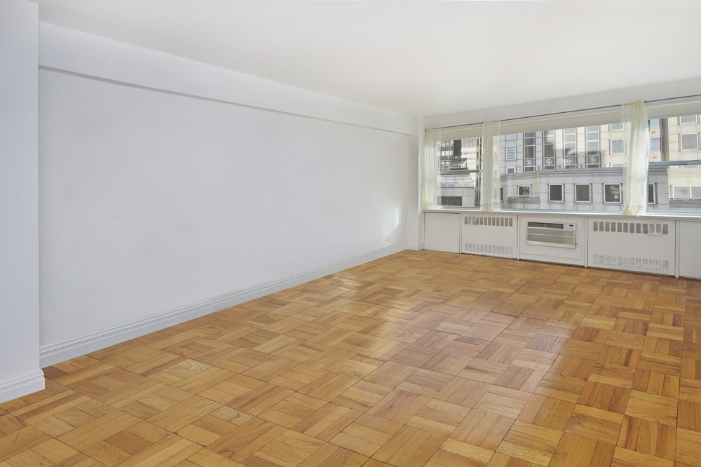 This is an empty bedroom with patterned hardwood flooring, white walls, white ceiling and a large window at the far end. Image courtesy of Toptenrealestatedeals.com.