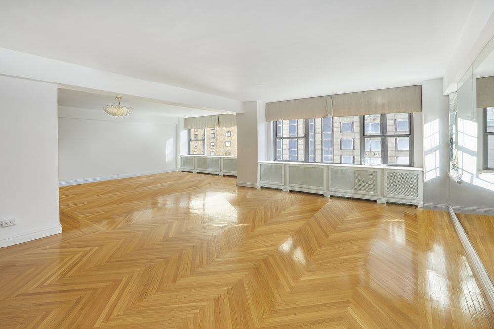 This is the spacious formal dining room with a herring bone hardwood flooring that pairs well with the white walls and ceiling brightened by the windows. Image courtesy of Toptenrealestatedeals.com.
