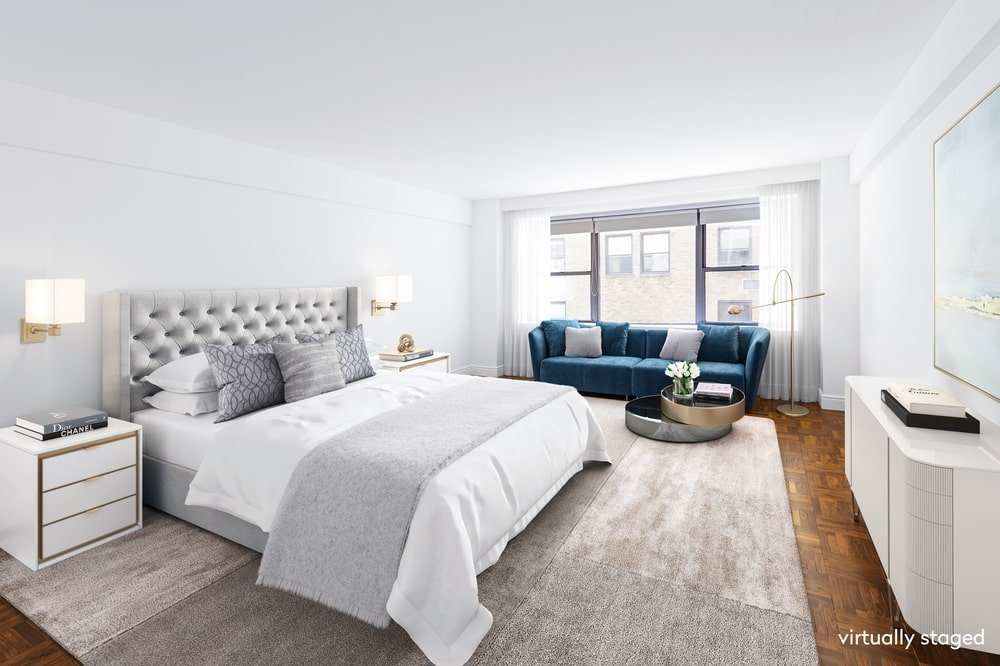 This is the primary bedroom that has a large gray tufted bed that pairs well with the area rug and the bright white walls. Image courtesy of Toptenrealestatedeals.com.