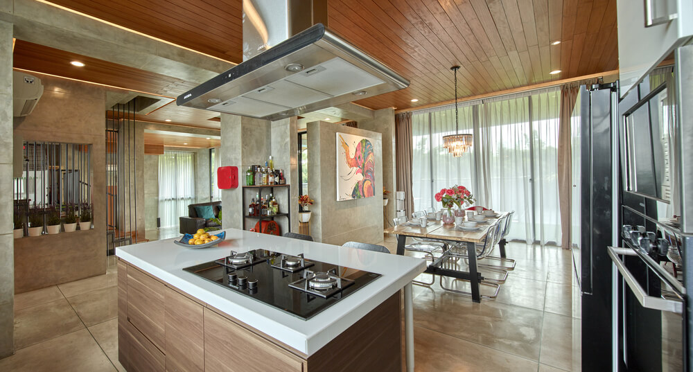 This is a view of the kitchen and the dining area on the far side with a large rectangular dining table by the glass wall.