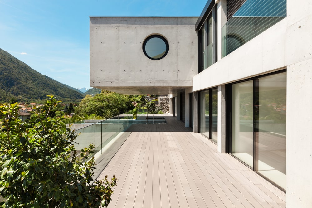 A look at the house balcony with a large concrete structure above it.