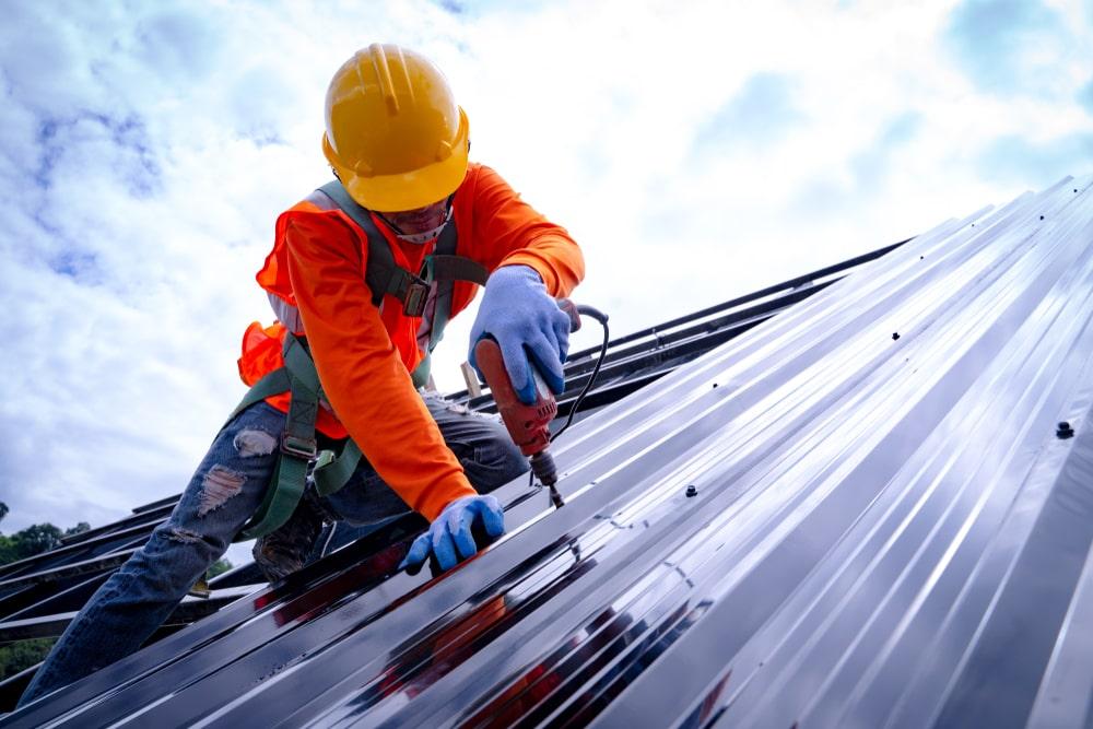 A metal worker putting bolts onto a metal sheet.