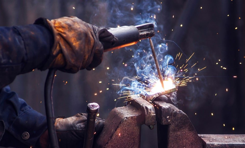 A close look at a welder welding two pieces of metal together.