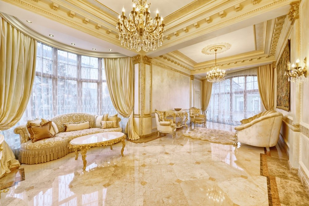 Mansion interior with marble tiled walls, floor-to-ceiling windows, ornate tray ceilings, and elegant furnishings.