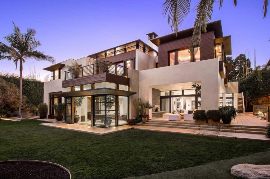 This is a look at the back of the mansion showcasing the large glass walls. dark brown exterior accents and the large private terrace of the upper floor. Image courtesy of Toptenrealestatedeals.com.