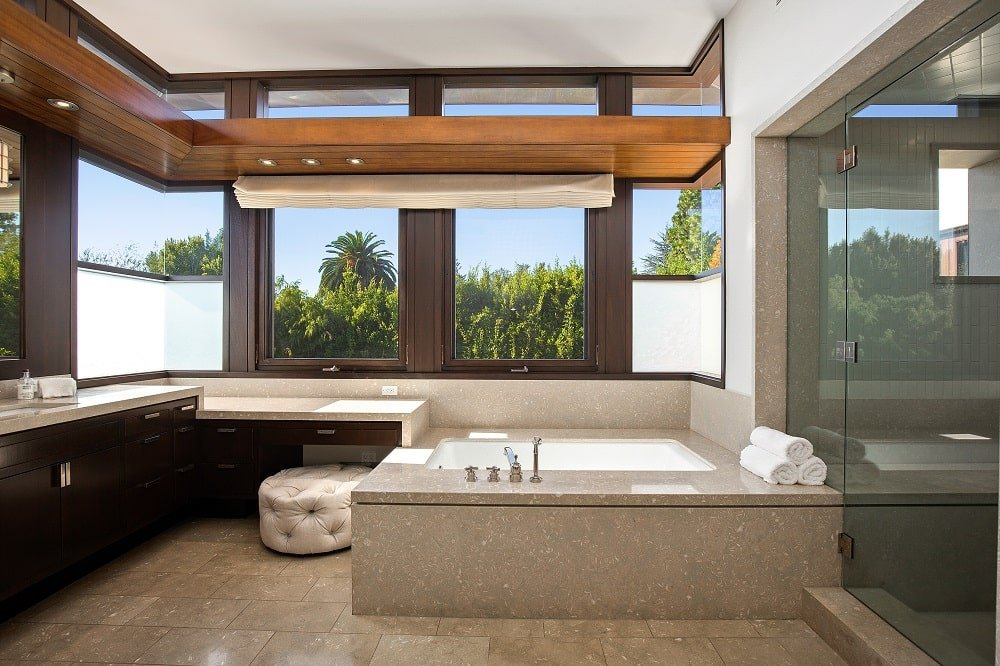 This is the bathroom that has a large bathtub housed in the same tiles as the floor contrasted by the dark cabinetry of the vanity and the glass door of the shower area. Image courtesy of Toptenrealestatedeals.com.