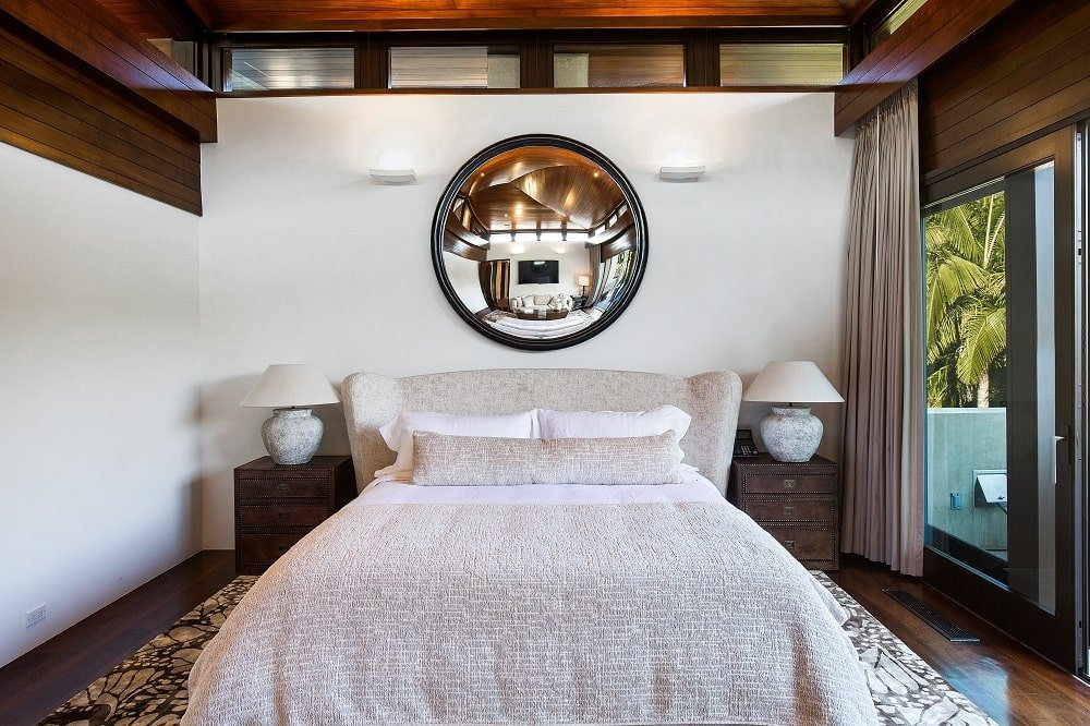 The primary bedroom has a large beige bed with cushioned headboard topped with a large circular wall-mounted mirror. Image courtesy of Toptenrealestatedeals.com.