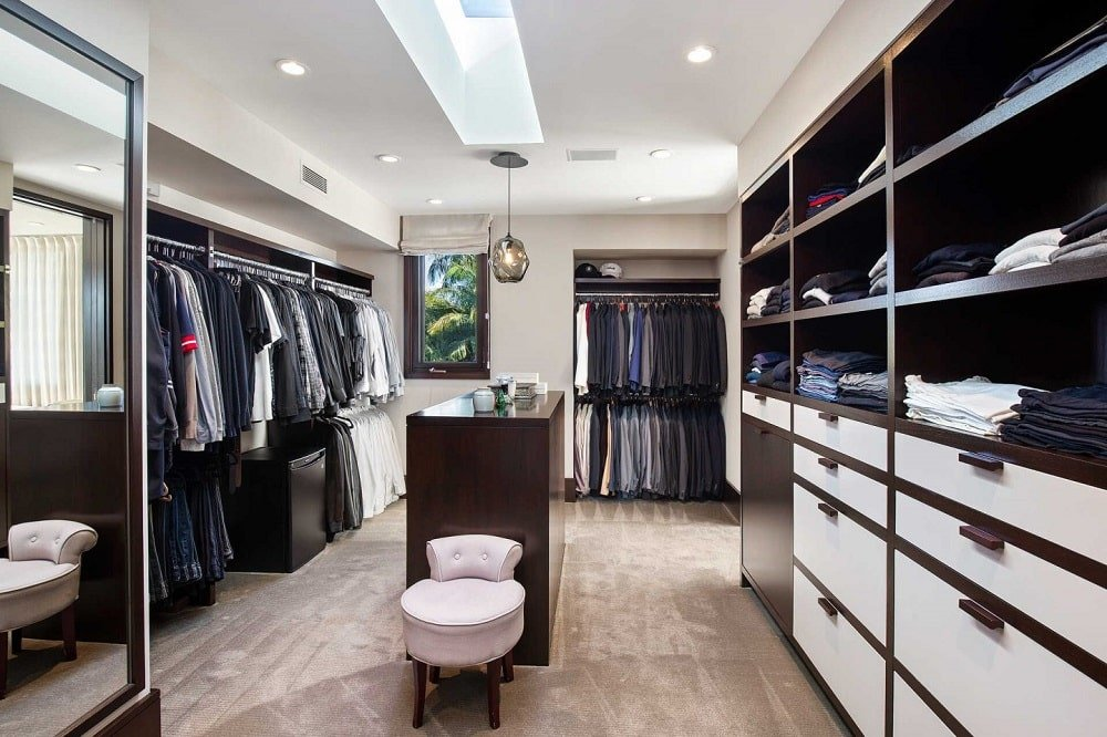 This closet has a small dark wooden island surrounded by built-in wooden cabinets, shelves, drawers and racks brightened by the white ceiling. Image courtesy of Toptenrealestatedeals.com.
