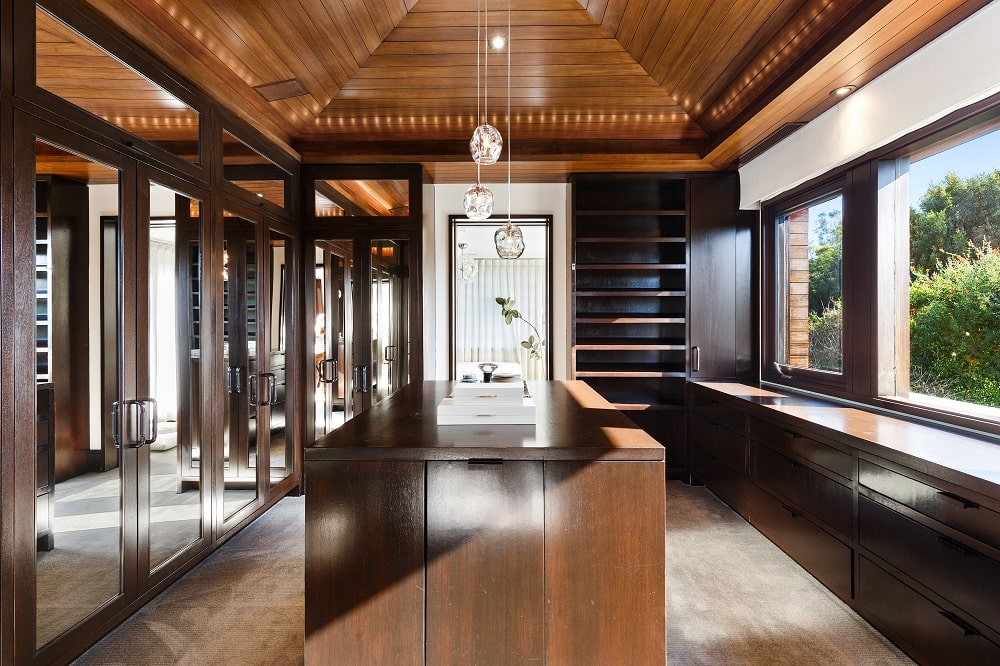 This is the other closet that has a large dark wooden island that matches the cabinets and drawers along the walls as well as the arched ceiling. Image courtesy of Toptenrealestatedeals.com.