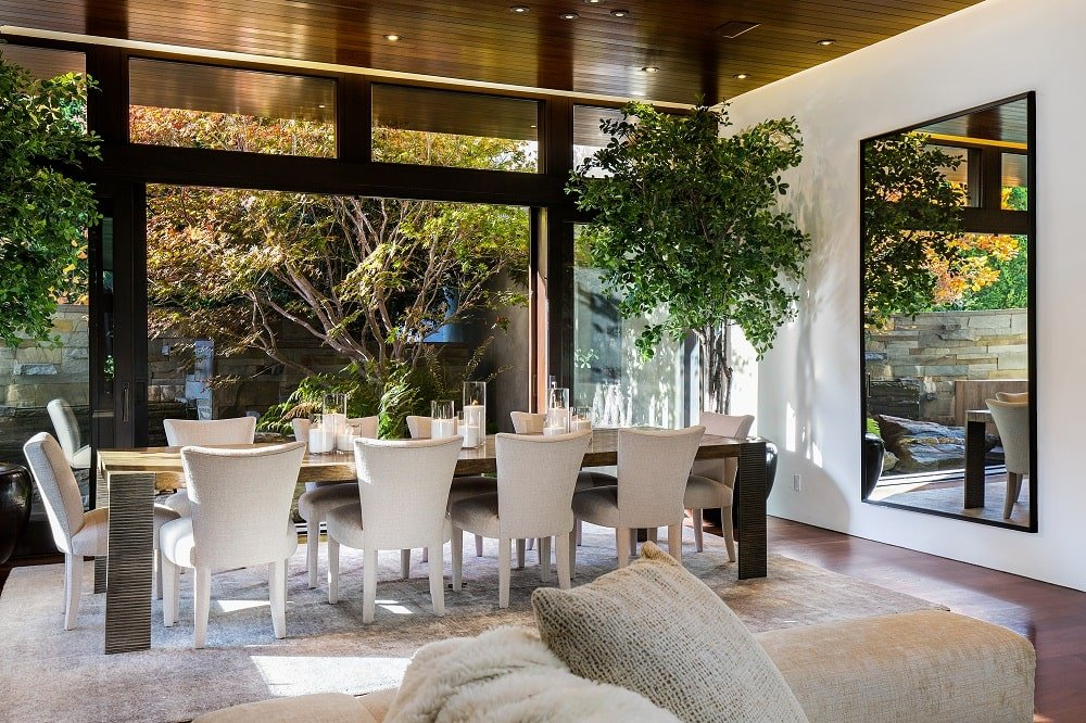 This is a close look at the dining area by the living room that has a large rectangular dining table surrounded by white chairs and adorned with a large potted plant. Image courtesy of Toptenrealestatedeals.com.