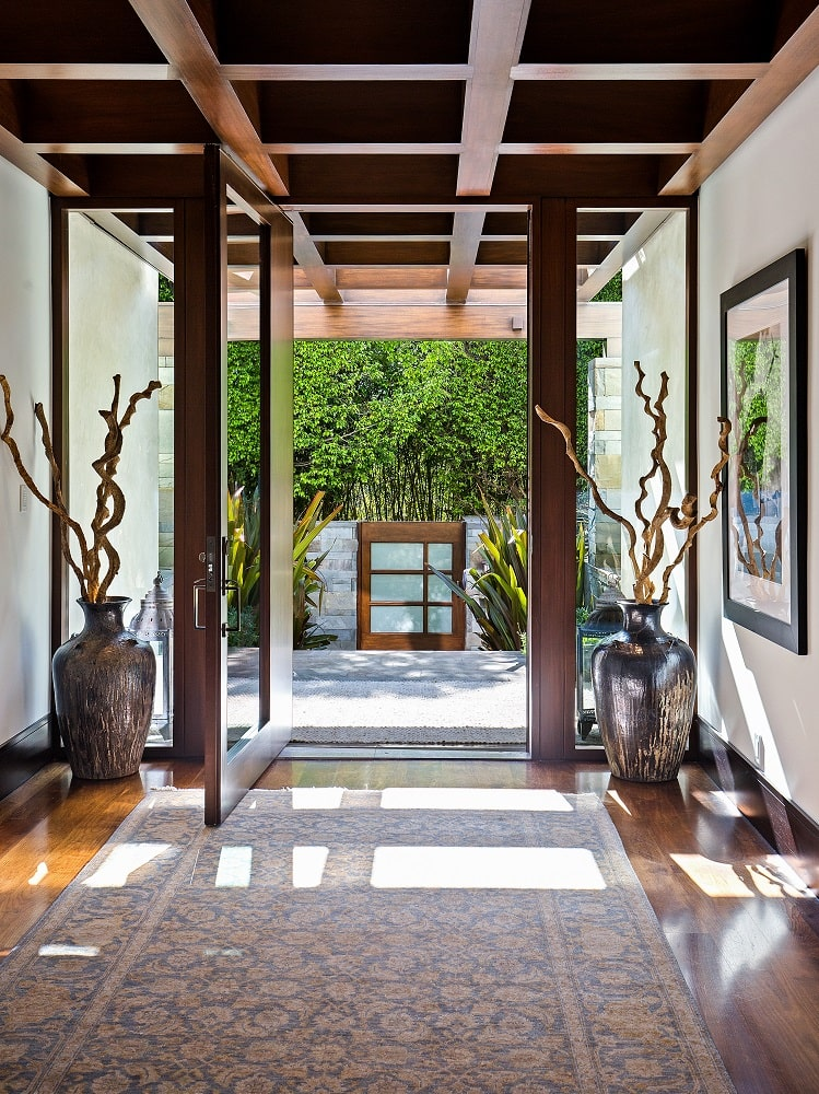 Upon entry of the house, you are welcomed by this bright foyer that has a wooden coffered ceiling that matches the wooden frames of the glass door and walls adorned with decorations. Image courtesy of Toptenrealestatedeals.com.