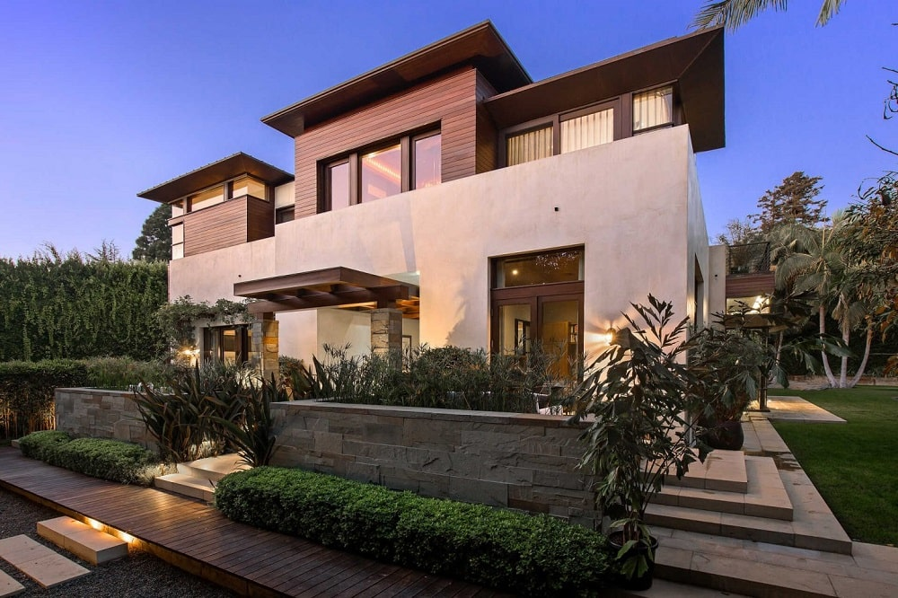 This is a look at the front of the house with planters and concrete steps leading to the main entrance that is topped with a cover. Image courtesy of Toptenrealestatedeals.com.
