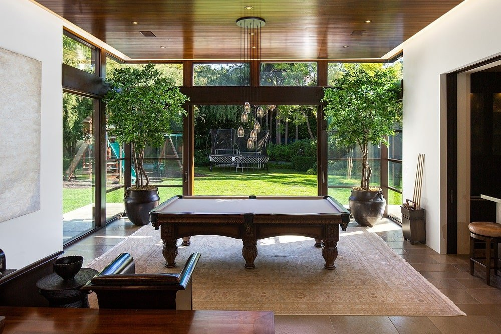 This is a look at the game area that has a large pool table surrounded by glass walls that bring in natural lighting. Image courtesy of Toptenrealestatedeals.com.