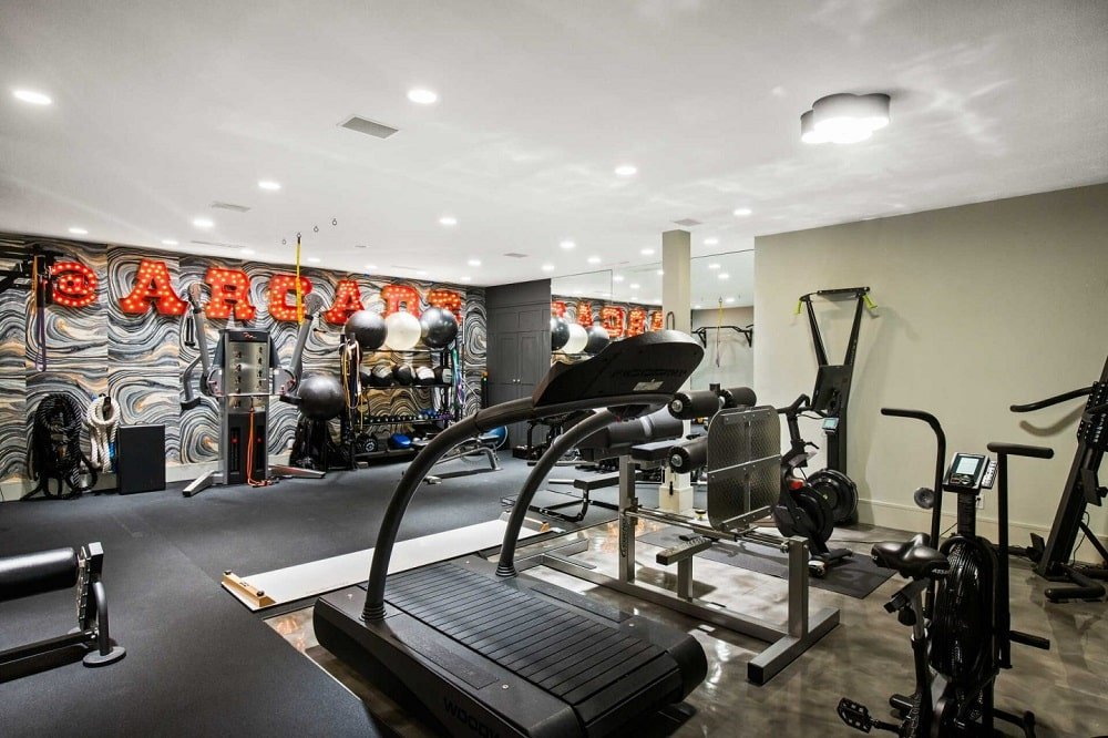 This is the large home gym with complete machines and equipment as well as mirrored walls and large wall decorations. Image courtesy of Toptenrealestatedeals.com.