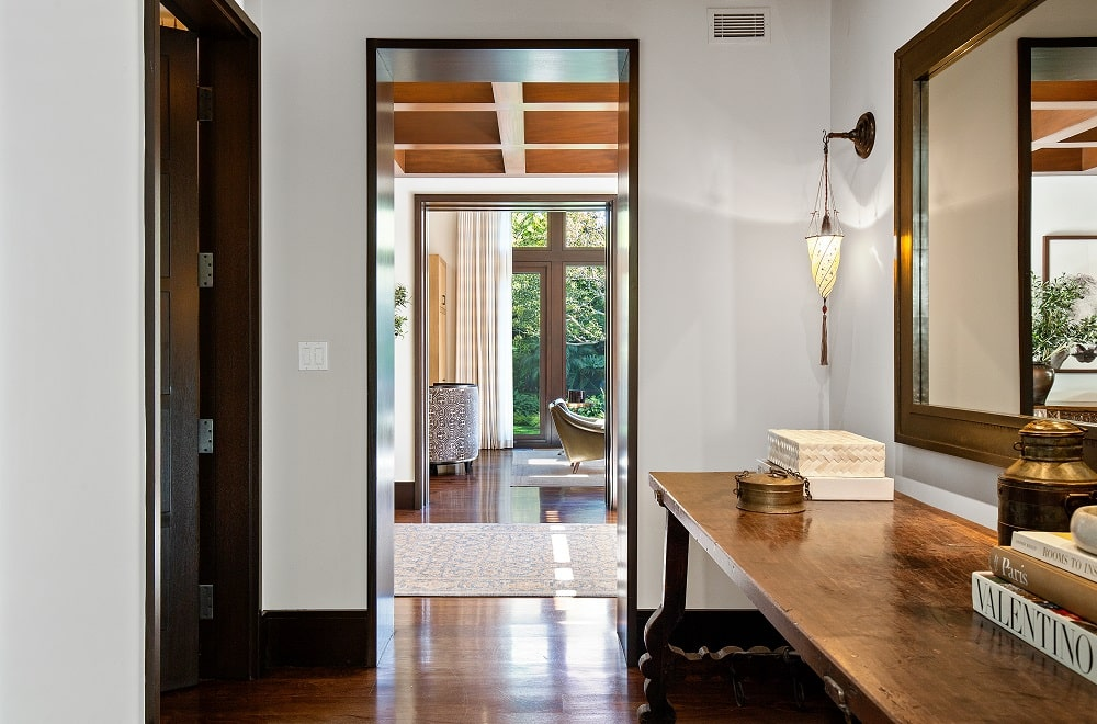 This is a hallway within the house that has a large wooden console table on the side topped with a mirror and wall-mounted lamps. Image courtesy of Toptenrealestatedeals.com.
