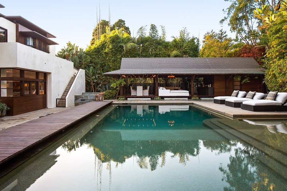 This is a look at the pool area with a wooden walkway on the side leading to the lanai on the far side. Image courtesy of Toptenrealestatedeals.com.