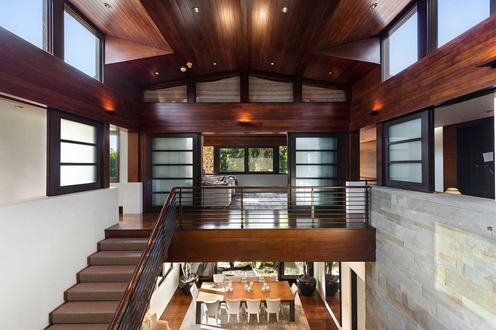 This is the second-floor landing above the living room with a dark hardwood flooring to match the tall ceiling and the stairs. Image courtesy of Toptenrealestatedeals.com.
