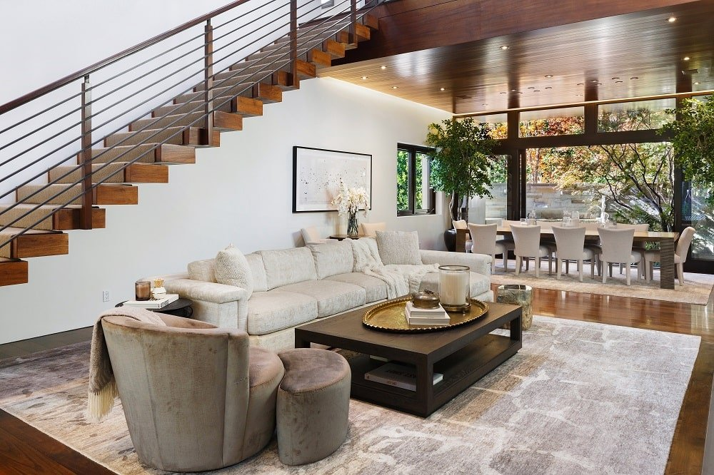 This is a close looka t the living room at the side of the staircase with a large beige sofa on a patterned area rug contrasted by the dark wooden coffee table. Image courtesy of Toptenrealestatedeals.com.