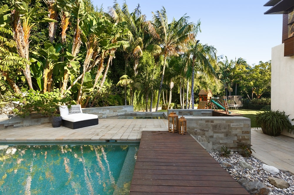 The side of the pool has a wooden walkway leading a sitting area by the pool with a background of lush tropical trees. Image courtesy of Toptenrealestatedeals.com.