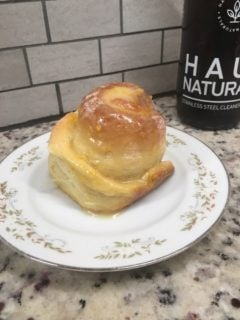 A freshly baked piece of orange sweet roll with icing.