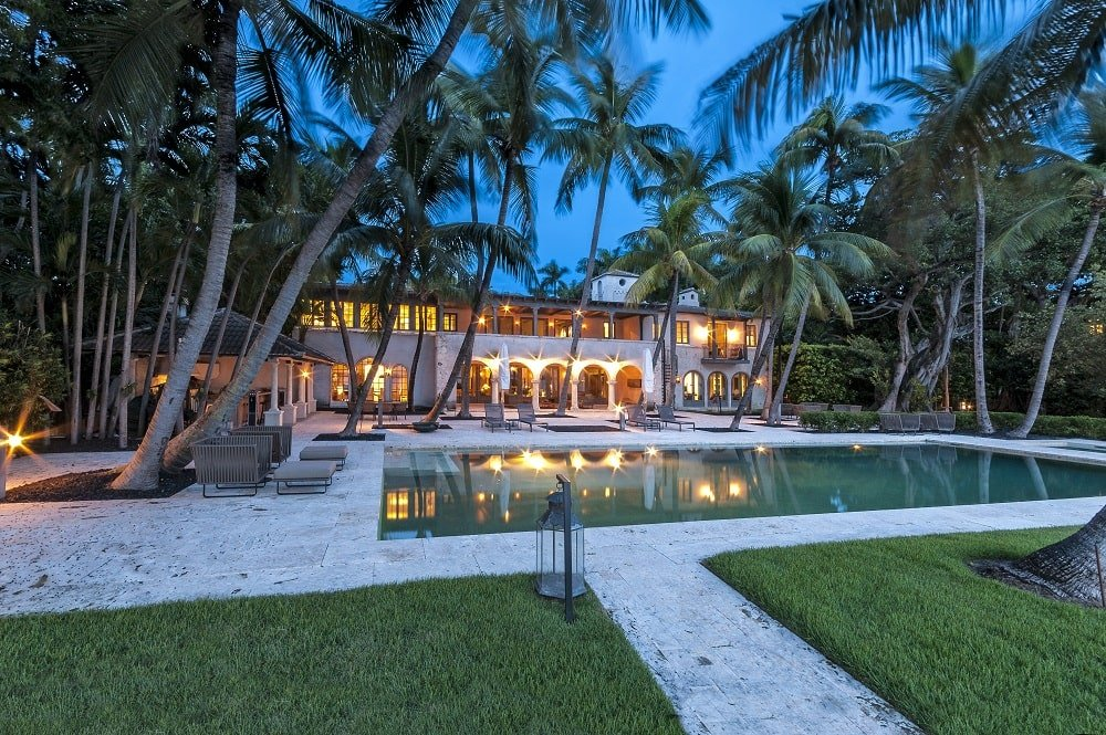 This is a nighttime view of the mansion from the vantage of the backyard pool. You can see here the warm glow of the house adorned by the multiple tall tropical trees. Image courtesy of Toptenrealestatedeals.com.