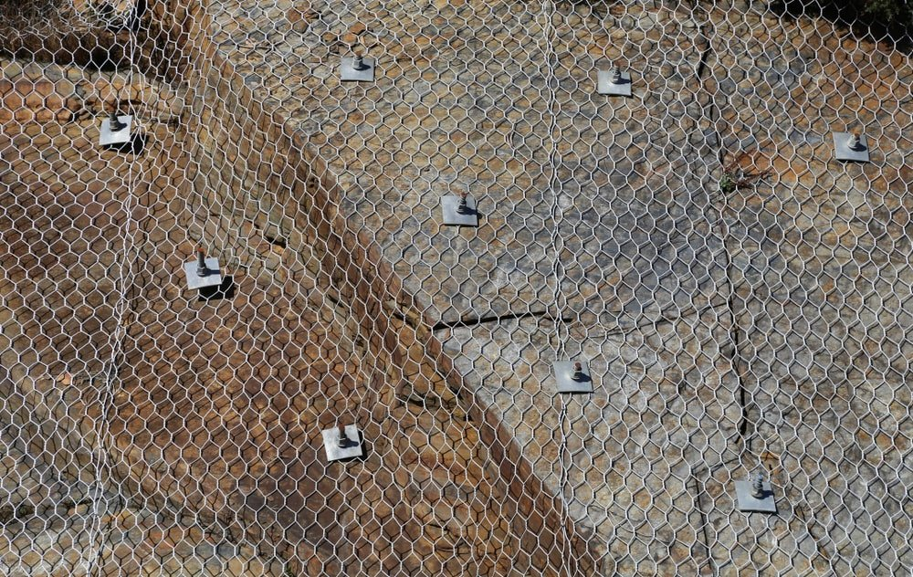 Rock face with wire netting and bolts.