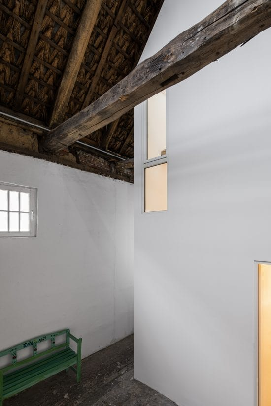 The white walls of the interiors are contrasted by the rustic wooden dark beams.