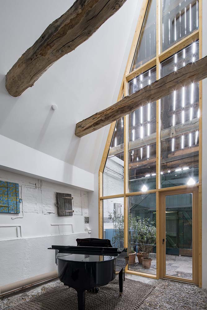 This is a look at the interior of the concrete structure that has a tall glass wall and large exposed log beams.
