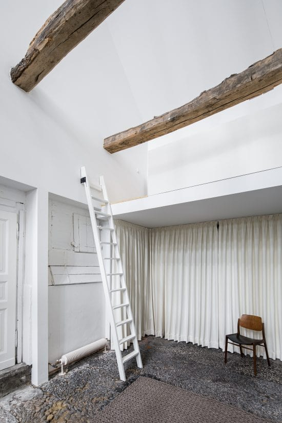 This is a corner of the house with a loft above accessed by a white ladder.