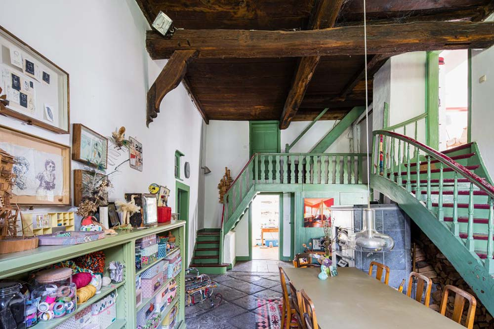 This is the interior of the house with green wooden structures and dark wooden beams above.