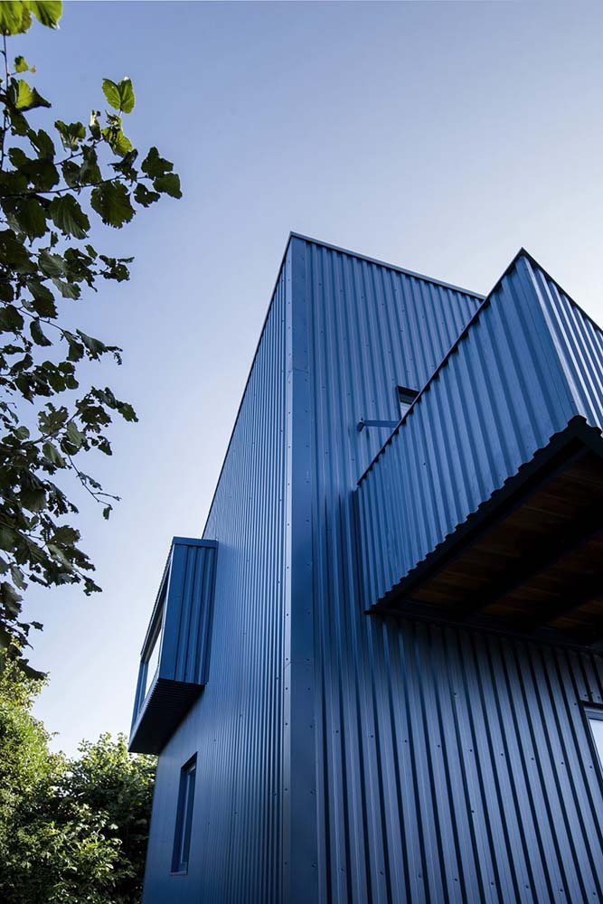 This exterior view of the house showcases its dark blue metal sheet exterior walls.