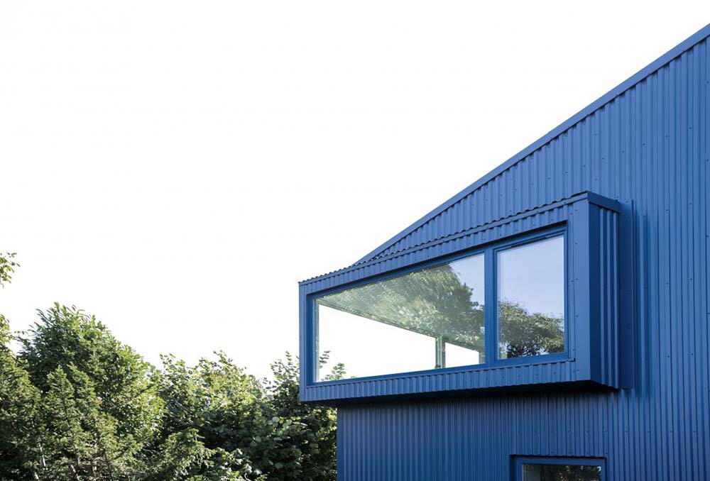 This is the upper level of the house with glass walls that stand out against the dark blue exterior walls.