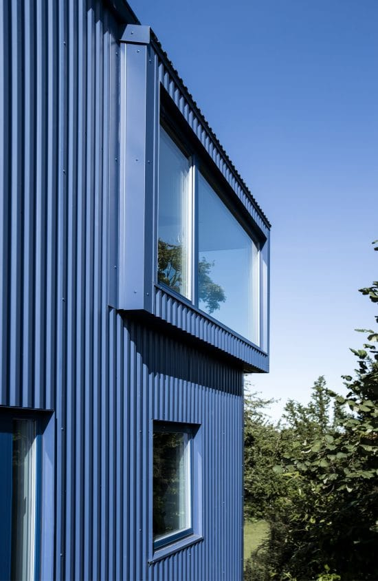 The large glass windows of the house stand out against the textured dark blue walls of the exterior.